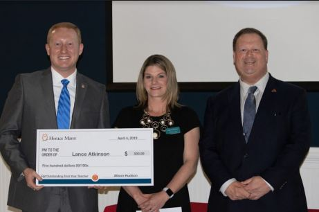 Johnston County Public Schools named Lance Atkinson (left) as the First Year Teacher of the Year at the annual Outstanding First Year Teacher of the Year Banquet on April 4. Standing with Atkinson is Alison Hudson (center) with Horace Mann Insurance Company who sponsored the award, and Johnston County Public Schools Superintendent Dr. Ross Renfrow (right).