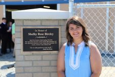 Shelby Bireley stands in front of the Shelby Rose Bireley Agricultural Building at Cleveland High.