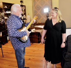 Benson native and legendary musician Jimmy Capps returned home last week to be honored by the town. Here he plays a few notes on a guitar he has loaned to the Benson Museum of Local History as Amy Adams watches. Daily Record Photo