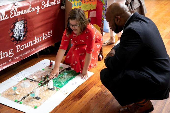 Kathleen Culbreth (left), student at Wilson's Mills Elementary, shares her classroom's model of an inclusive playground with guest De McKenzie (right), with RTI International Education Services.