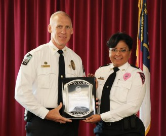 (Left to right) Clayton Police Chief Blair Myhand accepts the Fayetteville Cumberland Crisis Intervention Team Founders Award from Fayetteville Police Chief Gina Hawkins.