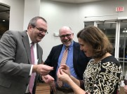 Dean of Campbell University's College of Pharmacy & Health Sciences, Dr. Michael L. Adams, gives Dr. Betsey Tilson a camel lapel pin. The Campbell University mascot is a camel.