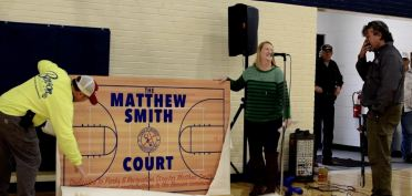 """The Lee Street gym court was named after Parks Director Matt Smith. The dedication was a complete surprise to him — something commissioners and town staff had managed to keep secret. Assistant Town Manager Kim Pickett made the announcement as Public Works Director Tim Robbins walked onto the court with a large sign reading, """"THE MATTHEW SMITH COURT."""""""