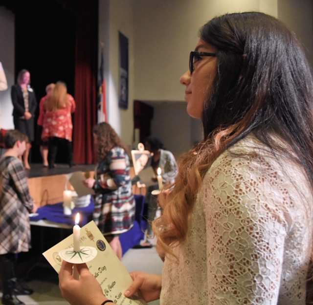 Wayne Community College student Tanya Avila-Diaz watches her fellow inductees receive their certificates, sign their names in the Upsilon Chi chapter record book, and light their candles during the recent Phi Theta Kappa Honor Society induction ceremony at the college.