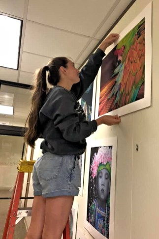Wayne Community College student Grace Boros, who serves as the lab assistant to Angie Waller, the college's art instructor, hangs a piece of art in an exhibition requested by Rep. John Bell IV.