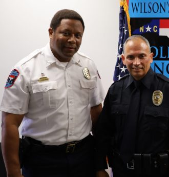 Wilson's Mill's Police Chief A.Z. Williams congratulates Officer Raymond Barton after he was sworn in this month as a part-time officer.