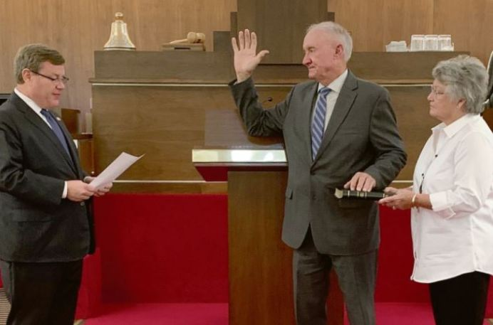 Former Harnett County Board of Commissioners Chairman Howard Penny takes the oath of office to fill the vacated District 53 North Carolina House of Representatives seat Thursday morning. Administering the oath is House Speaker Tim Moore and holding the Bible is Penny's legislative aid Grace Rogers.