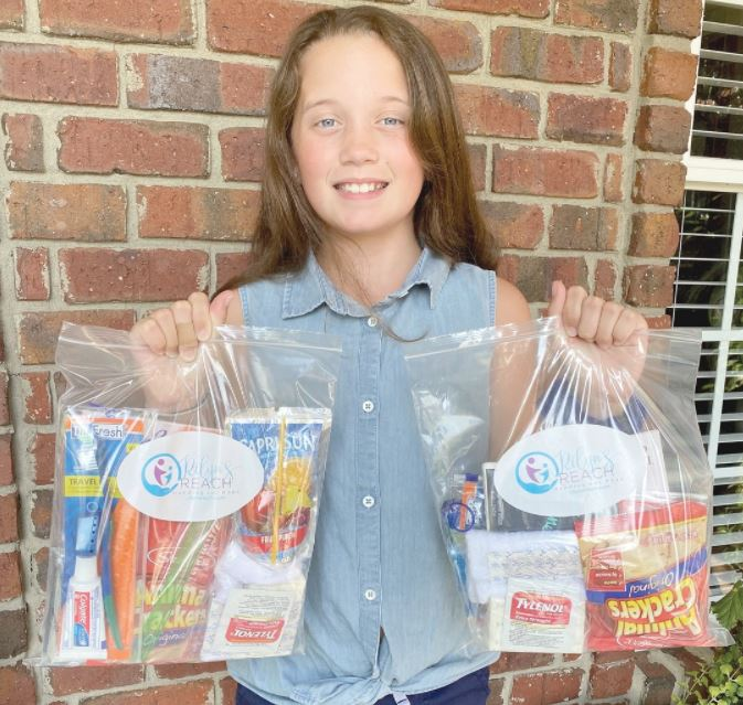 Rilyn Kerley, 10, stands with some of the care packages she delivered to SAFE of Harnett County. Each baggie was stuffed with toiletries, non-perishable snacks and an activity for adults and children. Contributed photo