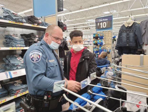 Dunn police Officer C. S. Keon looks for a pair of gloves with 12-year-old Dashawn Snead at Shop with a Cop at the Dunn-Erwin Walmart Tuesday morning. Dunn Daily Record Photo