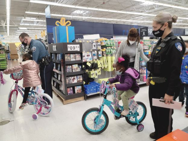 Dunn police Officer Christian Grant helps 3-year-old Eve Halsey round a corner on her new bicycle during Shop with a Cop Tuesday morning. Four-year-old Kaya Halsey, Quanisha Myles and Erwin police Officer Destiny Johnson follows behind. Dunn Daily Record Photo