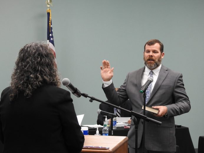 Commissioner Larry Wood takes his oath for a second term from Clerk of Court Michelle Ball.