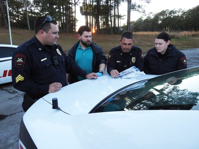 Four Oaks police officers examine evidence seized during a narcotics search warrant Monday afternoon at the Travelers Inn Motel on Highway 96.