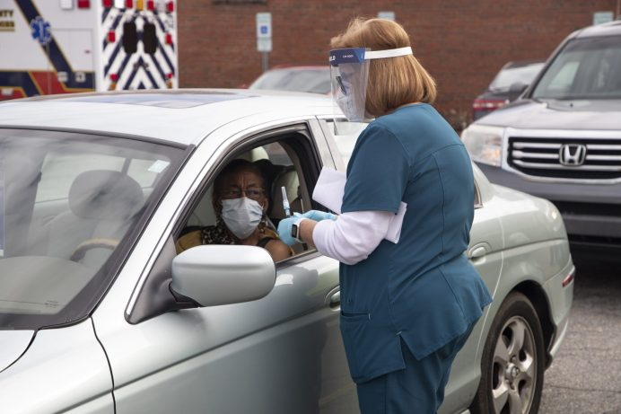 JCPS School Nurse Kathy Woodard (right) prepares to administer the Moderna COVID-19 vaccine to Special Assistant to the Superintendent Dr. Carolyn Ennis at a drive-thru vaccine clinic on Tuesday, Jan. 19.