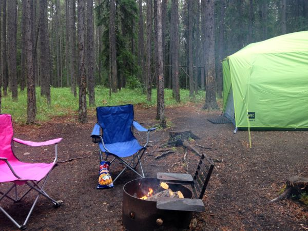 camp chairs by a fire and tent
