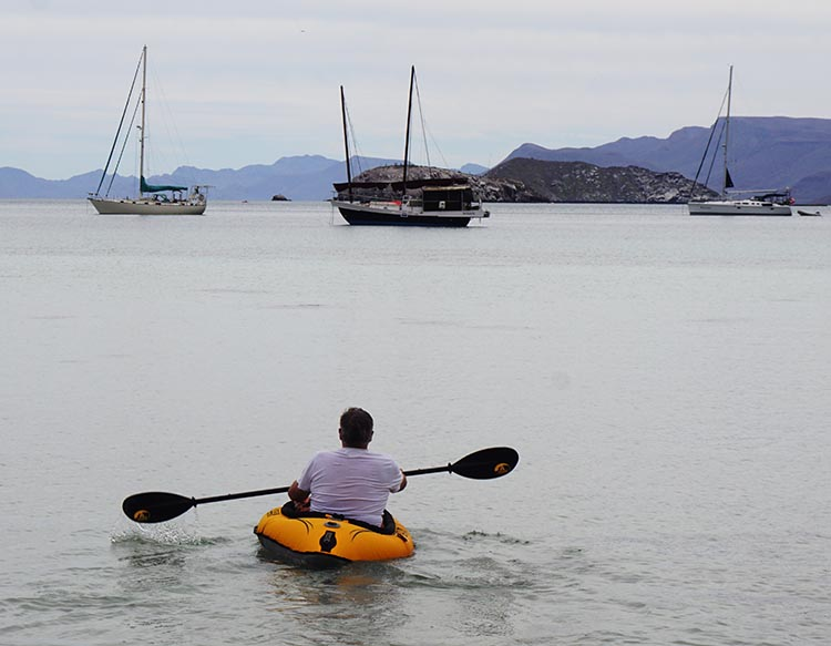 Our fellow traveler Jim Braun kayaking out directly in front of our rig on Santispac Beach, Bahia Concepcion