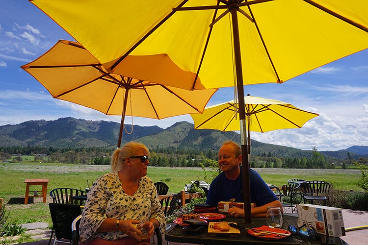 How to Get Free RV Camping with Harvest Hosts. Here are Joe and I, enjoying lunch and wine tasting at LongSword Vineyard in Jacksonville, Oregon. In the background is a field where hang gliders land, and further off are the vineyards