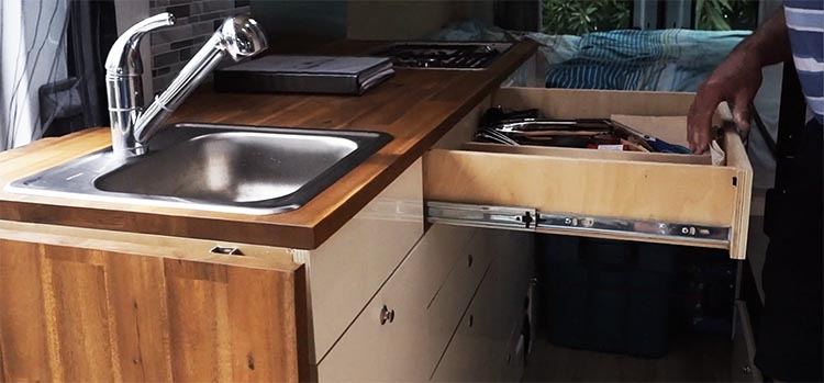 Video of Camper Van Conversion: How Marty Converted a Ford Transit into an RV Camper Van. The kitchen drawers have full extension hinges to make it easy to find things
