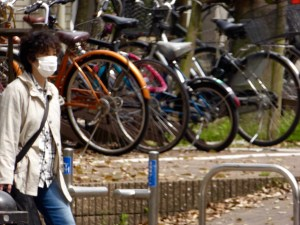 walker in Fukuoka, wearing mask; despite lots of bicycle use, pollution and pollen result in lots of masks.