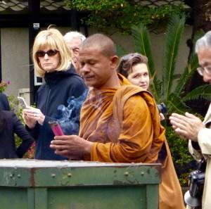 a monk at Kamakura lights incense before the Great Buddha