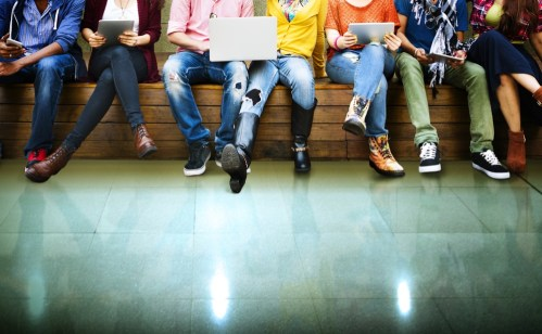 A bunch of teenagers sitting on a bench. Used on a page for teen counseling