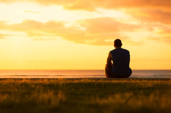 An image of a person sitting alone by the ocean. Used on a page for grief counseling