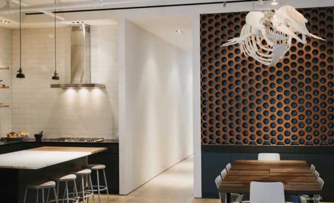 In this warm yet ultra-modern kitchen, the brick honeycomb wall serves as wine storage. A shark skeleton floats above the dining table.
