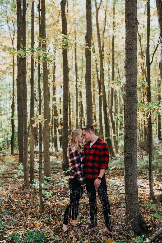 couple standing in front of a forest holding hands