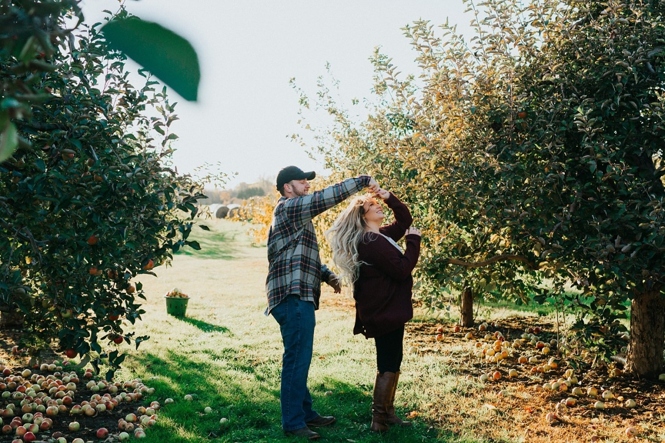 dancing in an apple orchard - fall engagement session couples posing idea