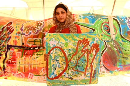 A young Syrian shows the work she's created in an art workshop