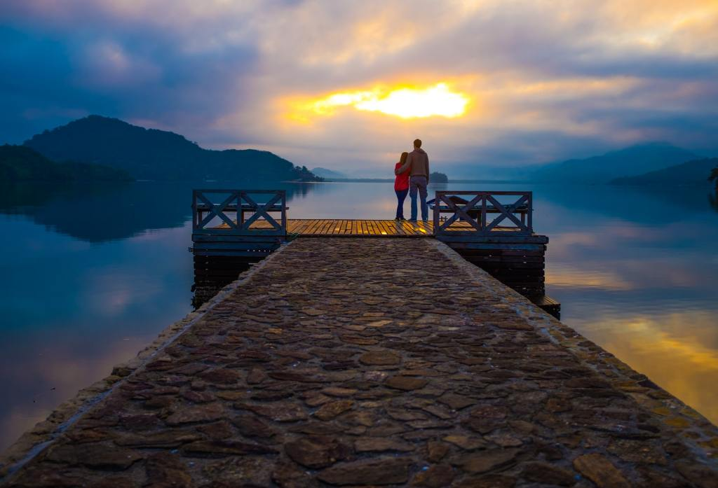 Couple on dock looking at sunset