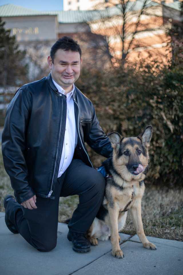 Joe with leather jacket kneeling next to matthew both looking at the camera, Joe smiling