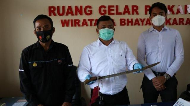 polisi menunjukkan alat bukti kejahatan berupa pedang yang dipakai