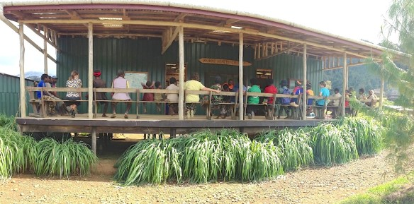 On the veranda of the clinic, Ben Samauyo preaches the Word to waiting patients. (Oct. 2015)