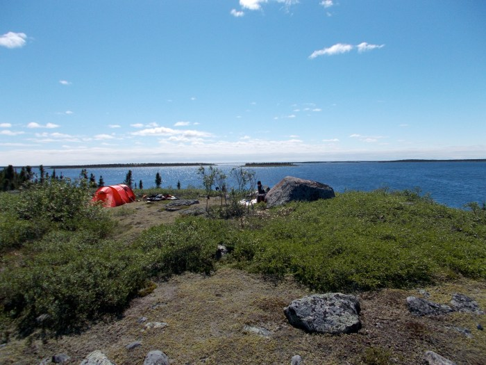 View looking south down Boyd Lake from our hilltop camp, Kate is beside the big rock starting to sort the food drums
