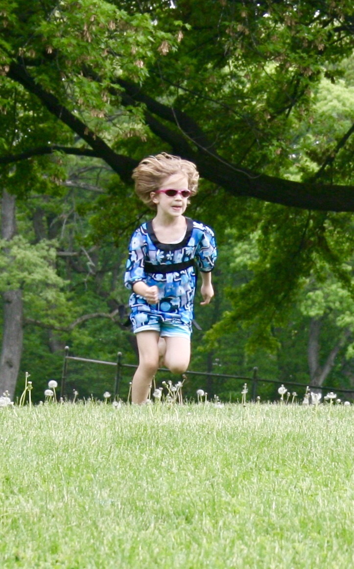 girl running in dandelions