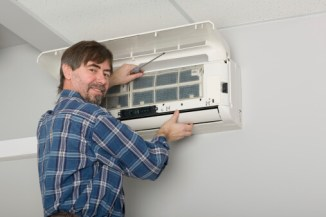 John Betlem Heating and Cooling, Inc. technician working on a ductless unit.