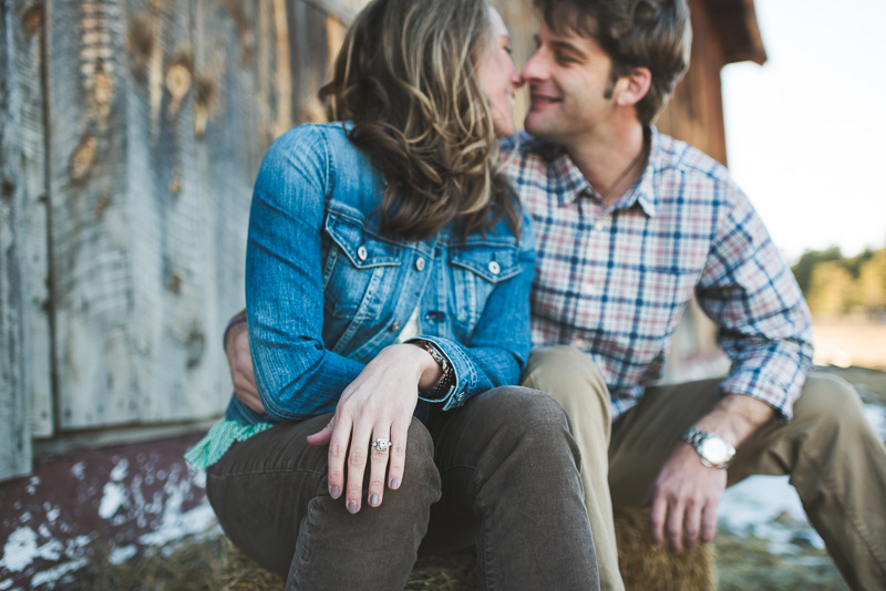 evergreen engagement photos by a rustic barn