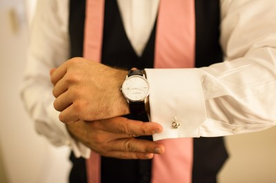 groom adjusts cufflink with untied tie