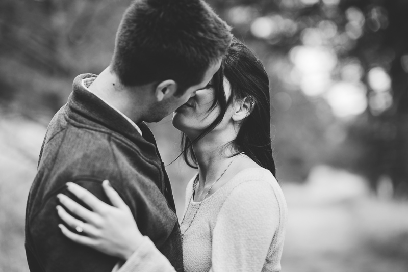 Evergreen engagement photography kissing couple in a forest black and white