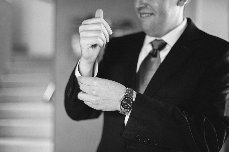 Golden Wedding Photographer groom fixing cuffs