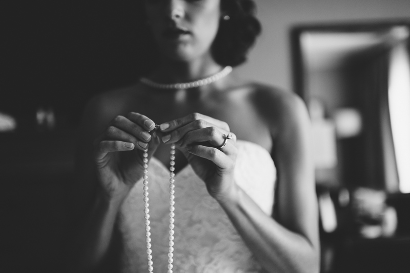 Boulder Wedding Photography bride putting necklace on