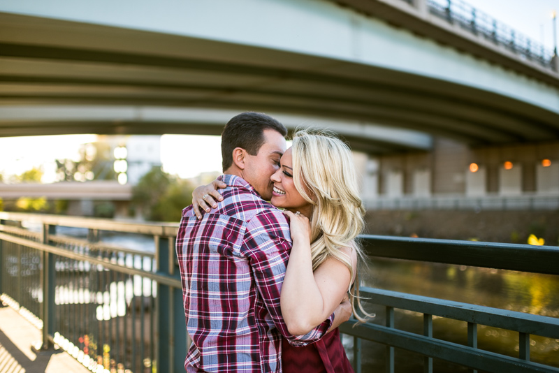 Denver Engagement Photography hugging in front of bridge