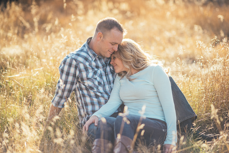 Denver Engagement Photographer couple sitting in field of grass