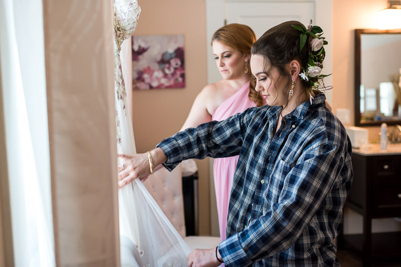 deer park villa wedding photography bride looking at dress