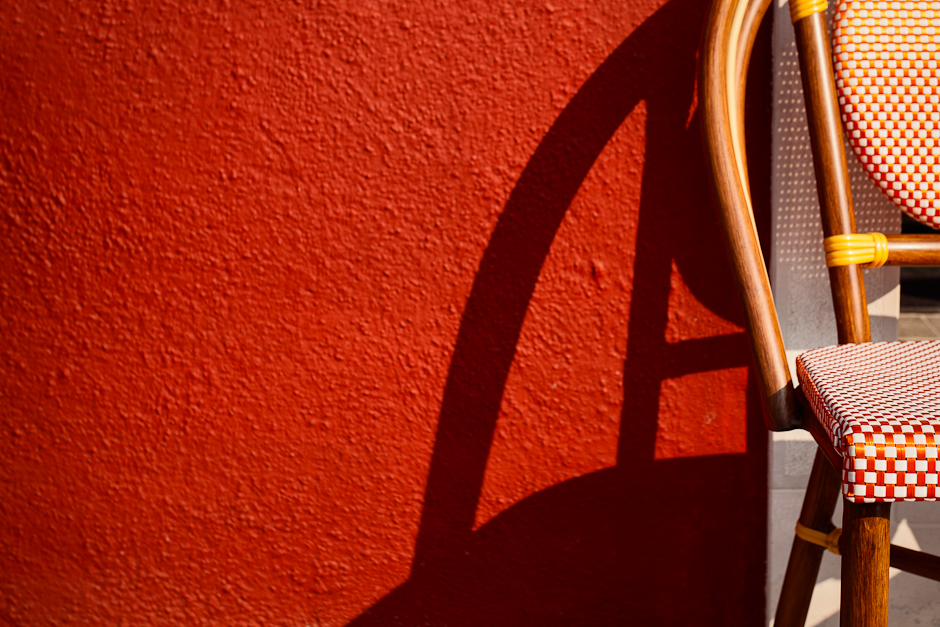 Image of a chair against a red wall in the Italian Island of Burano in Venice