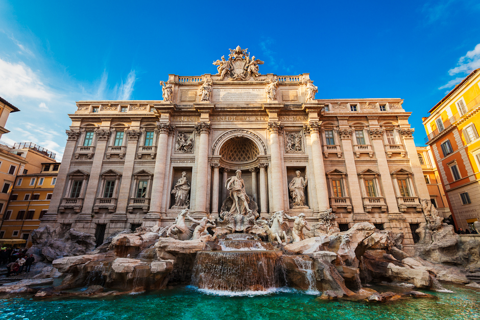 Photograph of the Trevi Fountain in Rome, Italy, in the late afternoon with blue skies