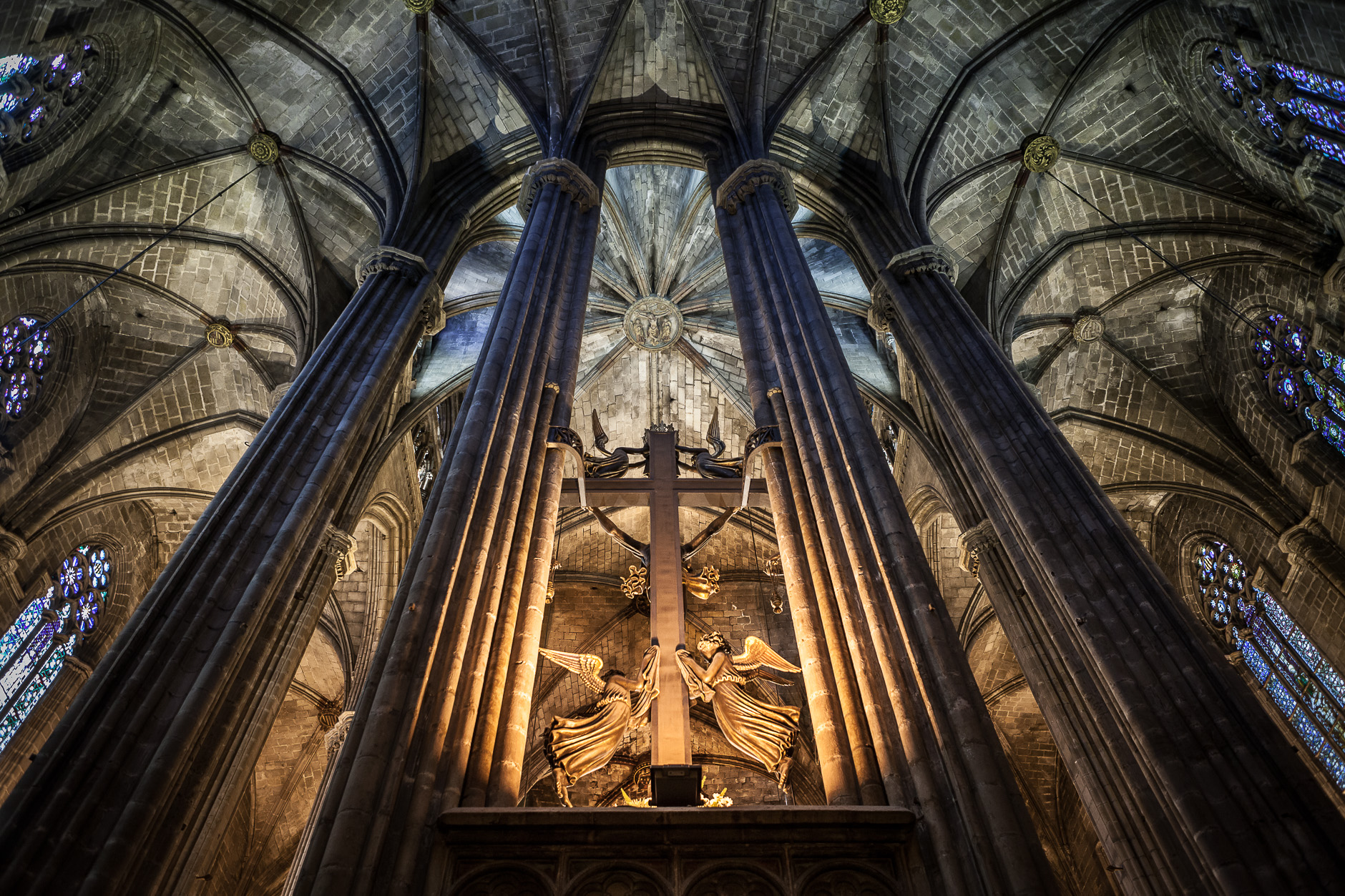 Image of the inside of the Barcelona Cathedral, showing the back of the altar, a cross and angels