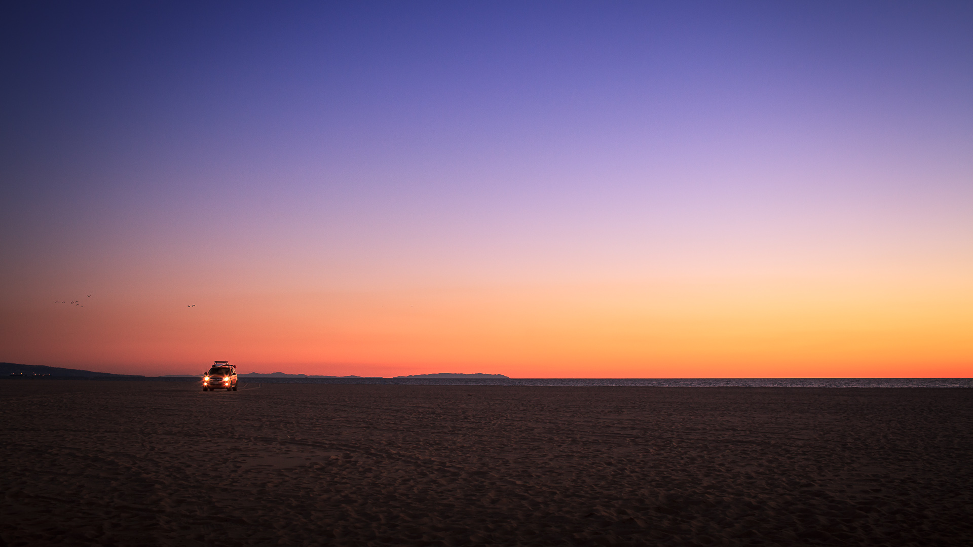 Sunset at Santa Monica beach, with a car over the sand