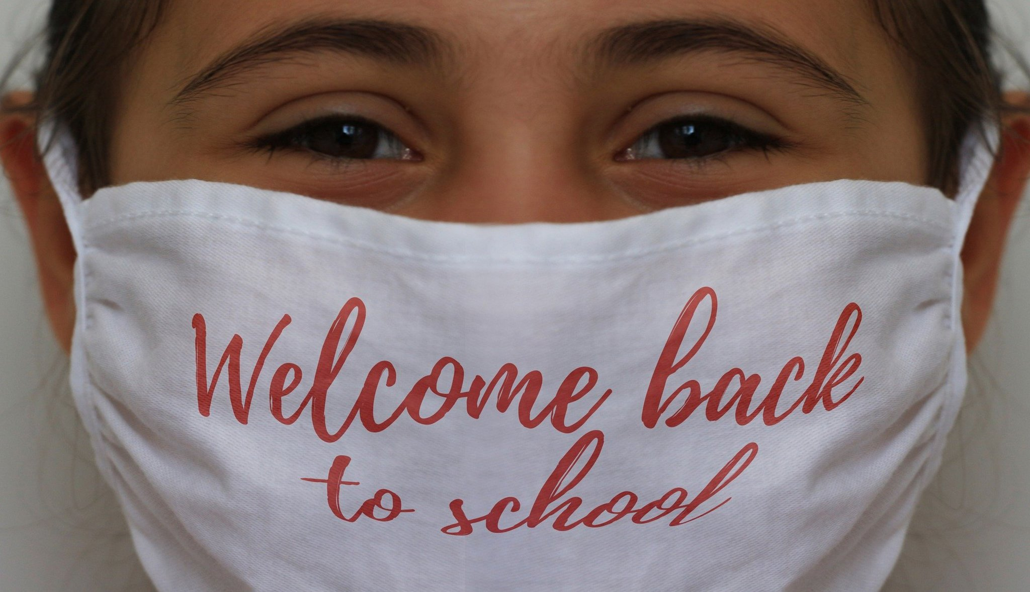 Girl wearing face mask on which is printed 'back to school'