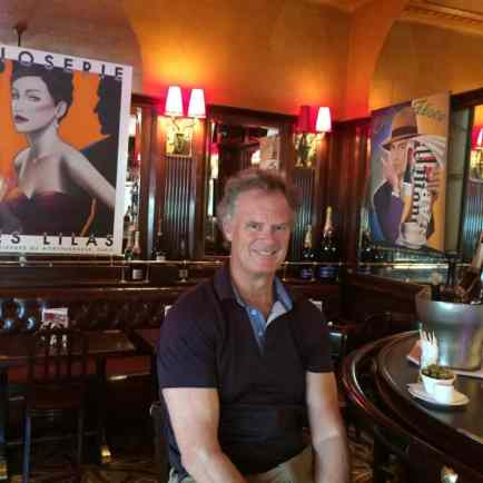 "Me in Ernest Hemingway's old barstool in La Closerie des Lilas where he penned much of ""The Sun Also Rises."""